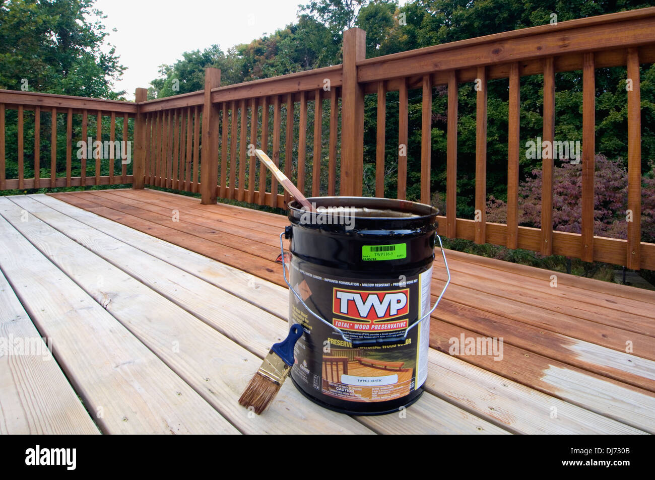 Five Gallon Bucket of Wood Stain and Preservative on Partially Stained Deck - Stock Image