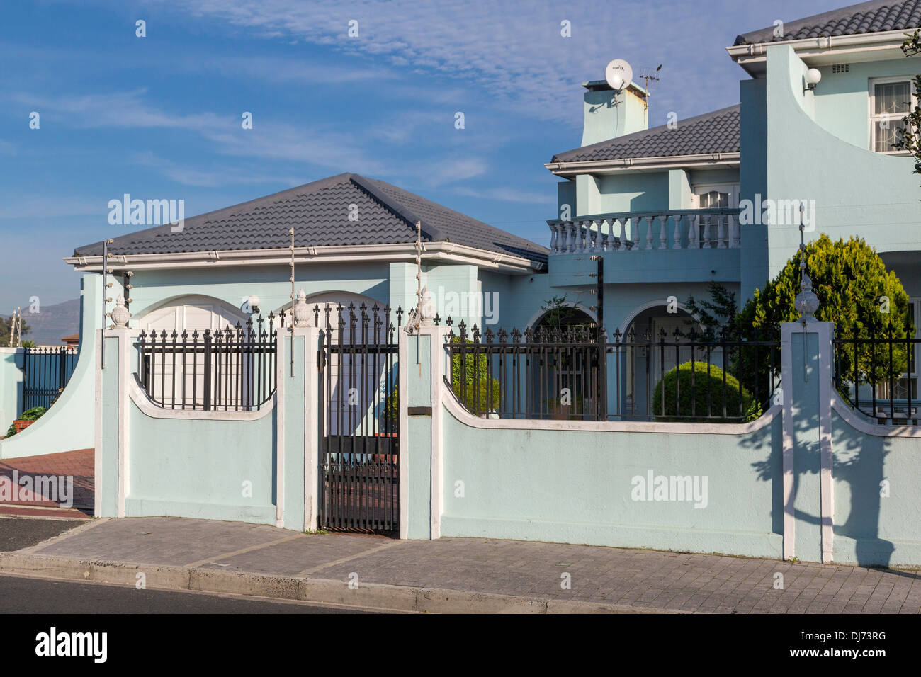 South africa cape town athlone suburb security alarm wires atop wall surrounding upper class house