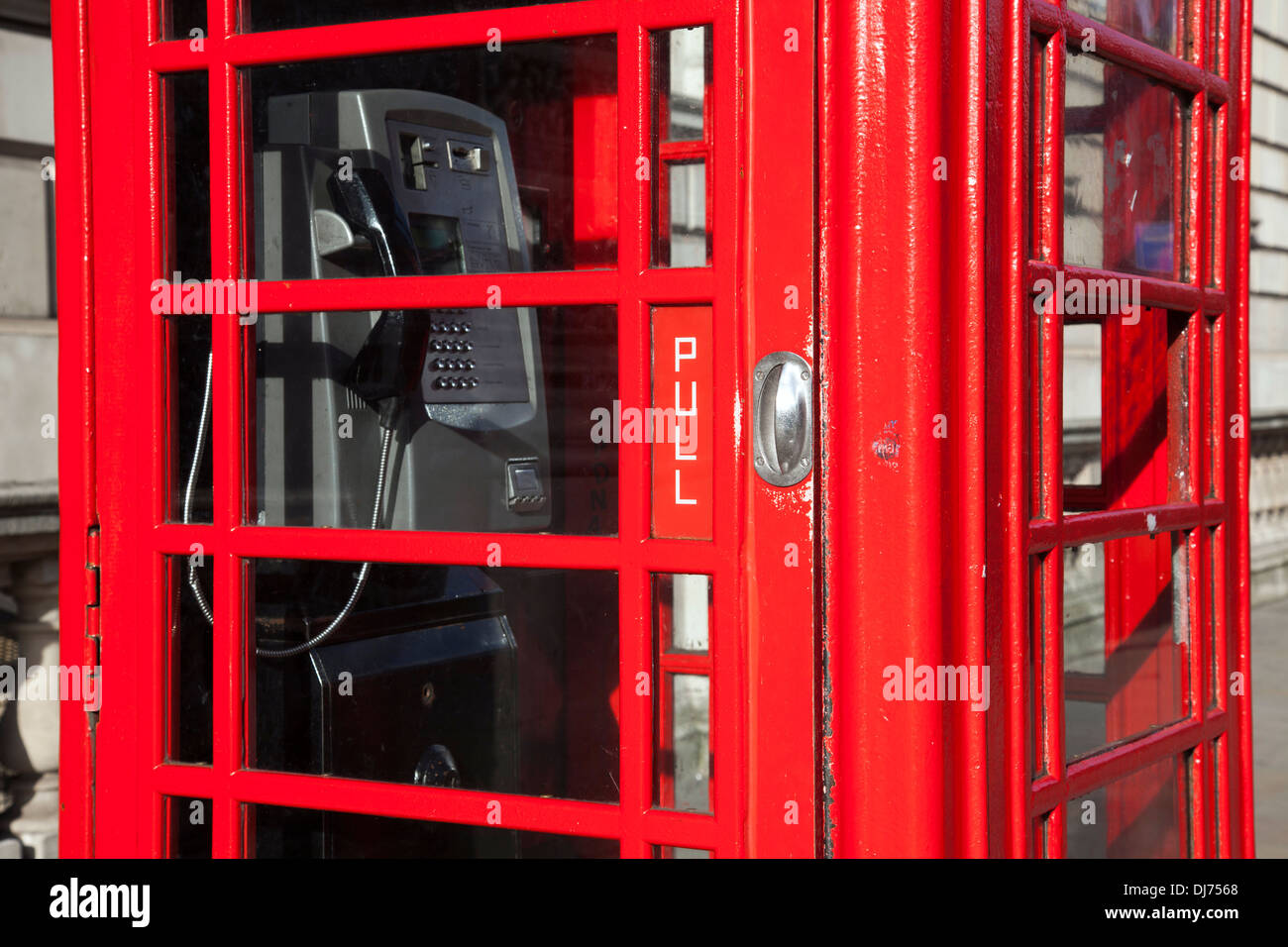 A red telephone box with pay phone in the U.K. - Stock Image