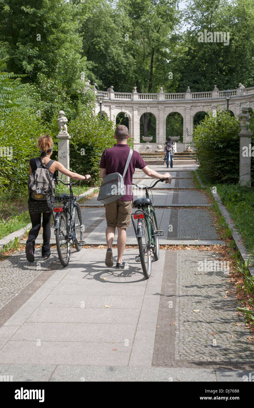 Two Cyclist at the Volkspark Friedrichshain Park by the Marchenbrunnen Fairy Tale Fountain, Berlin, Germany - Stock Image