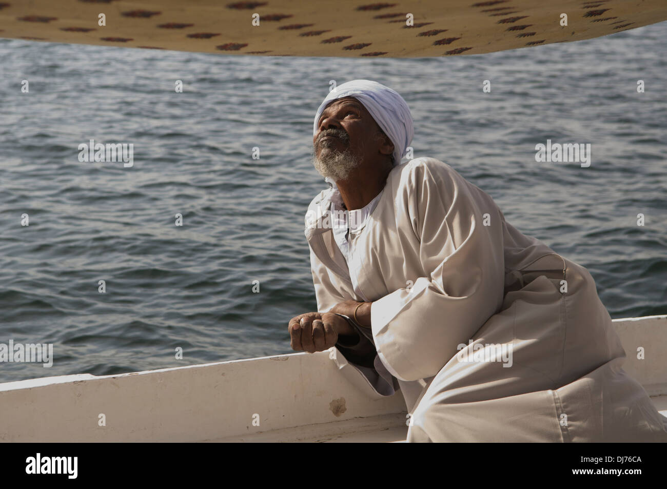 Felucca pilot checking his sail while on the Nile, at Aswan, Egypt. - Stock Image