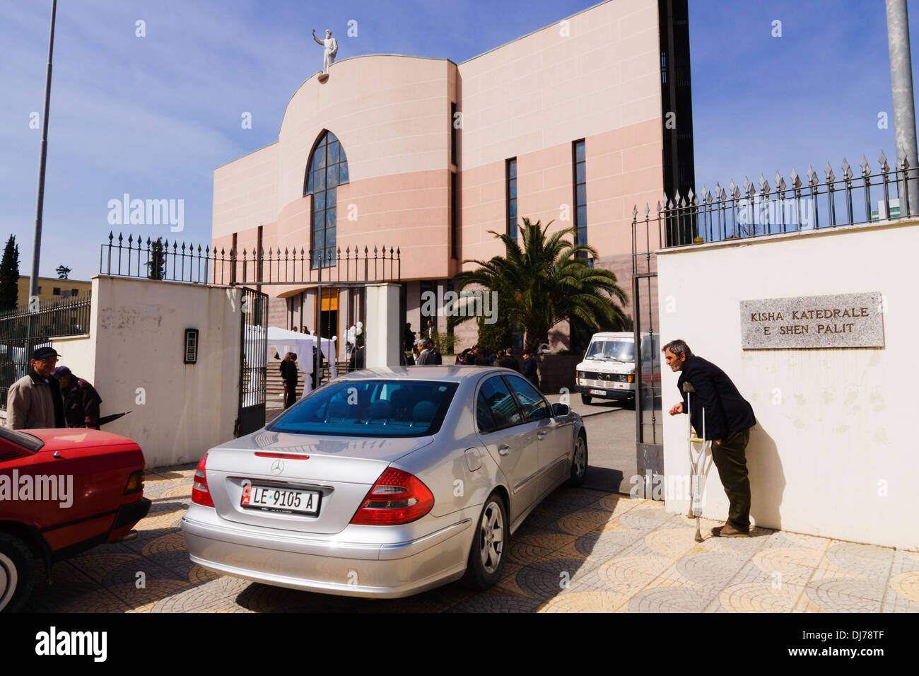 Beggar and luxury car at the entrance of St Paul's Catholic Cathedral. Tirana, Albania - Stock Image