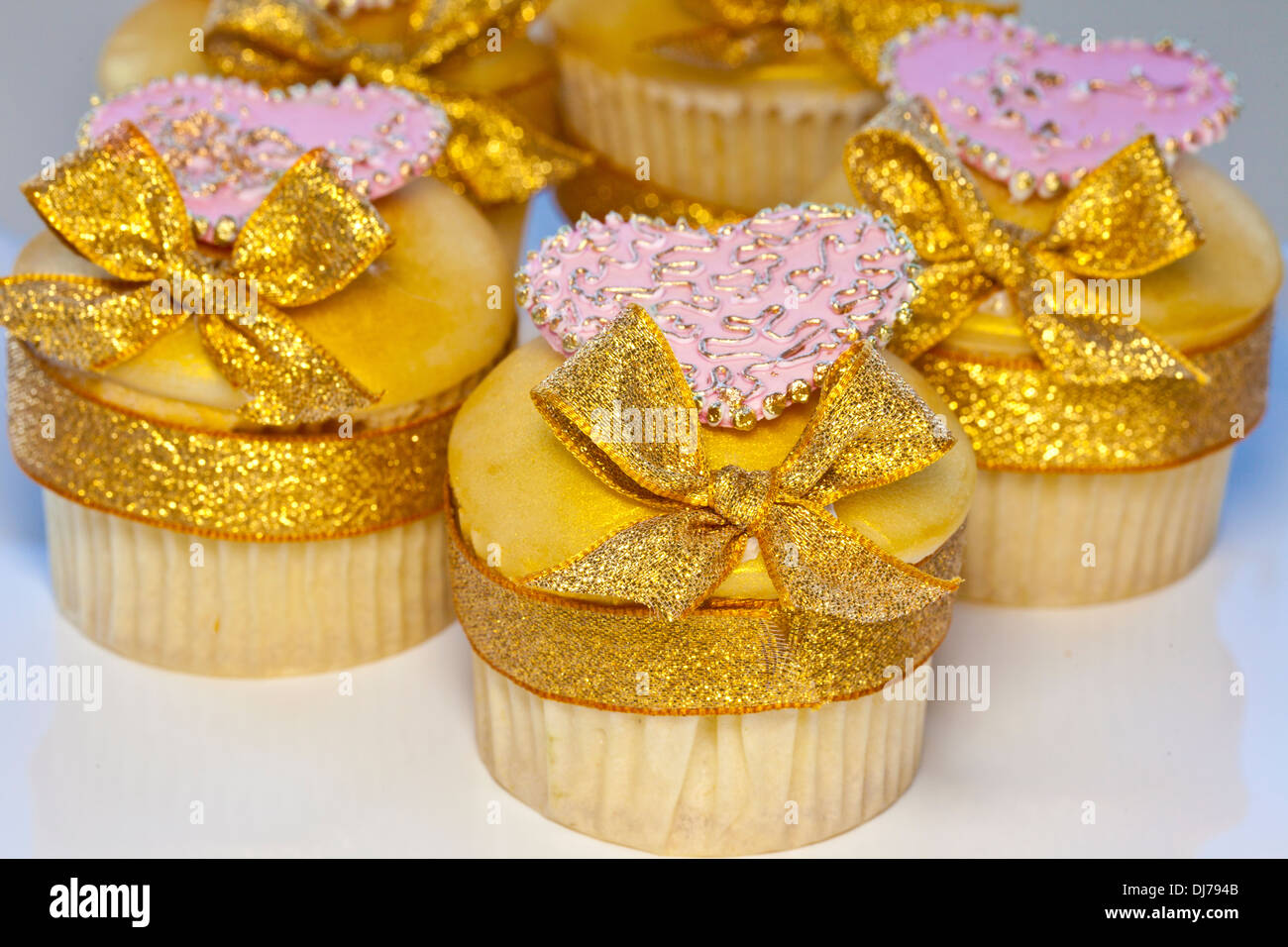 Cupcakes decorated with golden icing and bows also pink hearts. - Stock Image