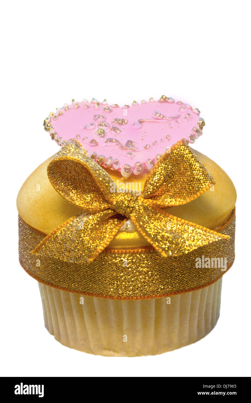 Cup cake decorated with golden icing and bow also pink heart isolated on white. - Stock Image