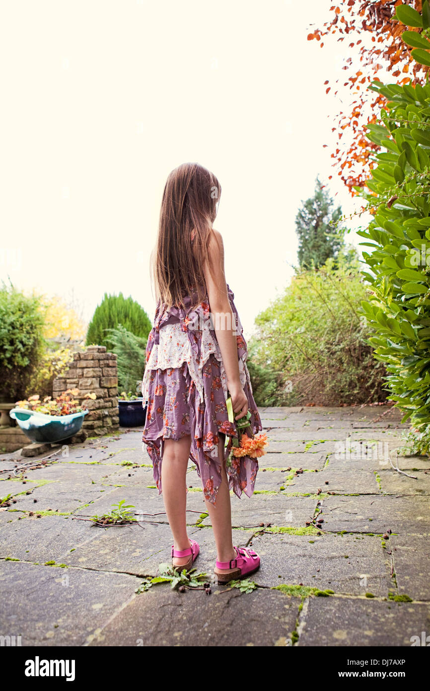 Girl outdoors in ragged dress, looking away from the camera on a summer day. - Stock Image