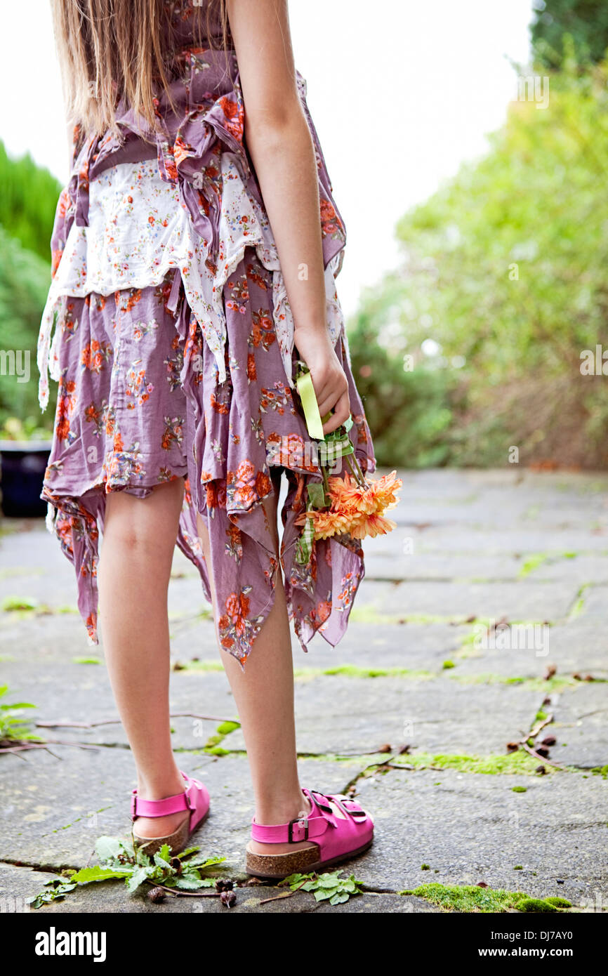 Low section of girl on a warm summers day in a ragged dress, holding a bunch of flowers. - Stock Image