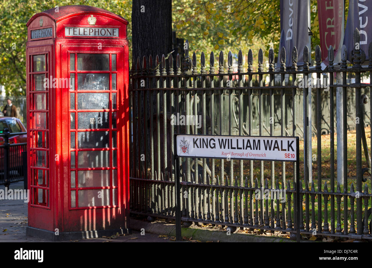 A traditional red telephone box against a iron railing in King William Walk, Greenwich, London - Stock Image