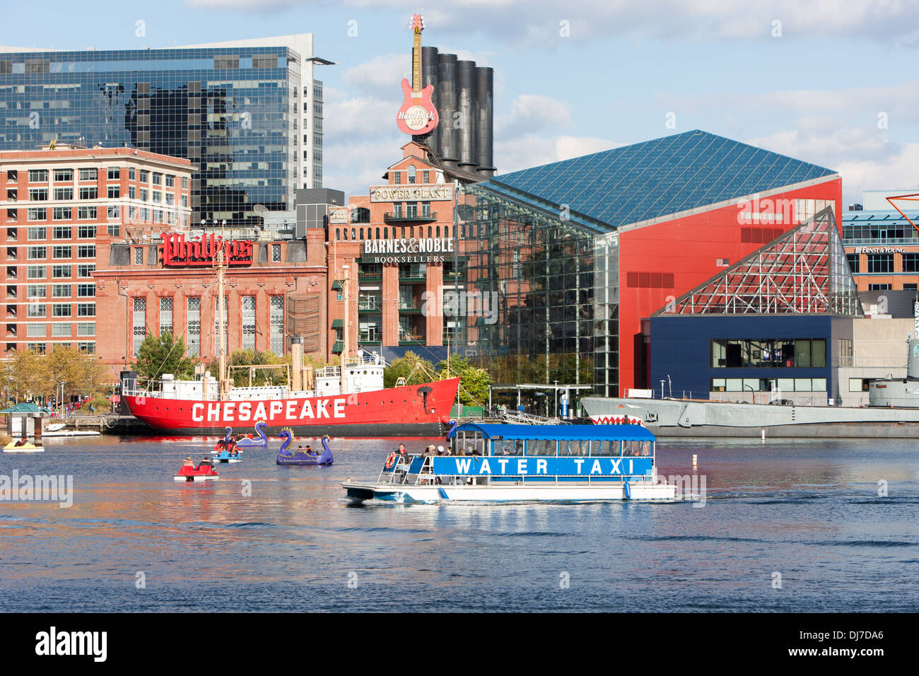 Tourists enjoy paddle boats as a Water Taxi approaches the Harborplace landing in the Inner Harbor of Baltimore, Maryland. - Stock Image