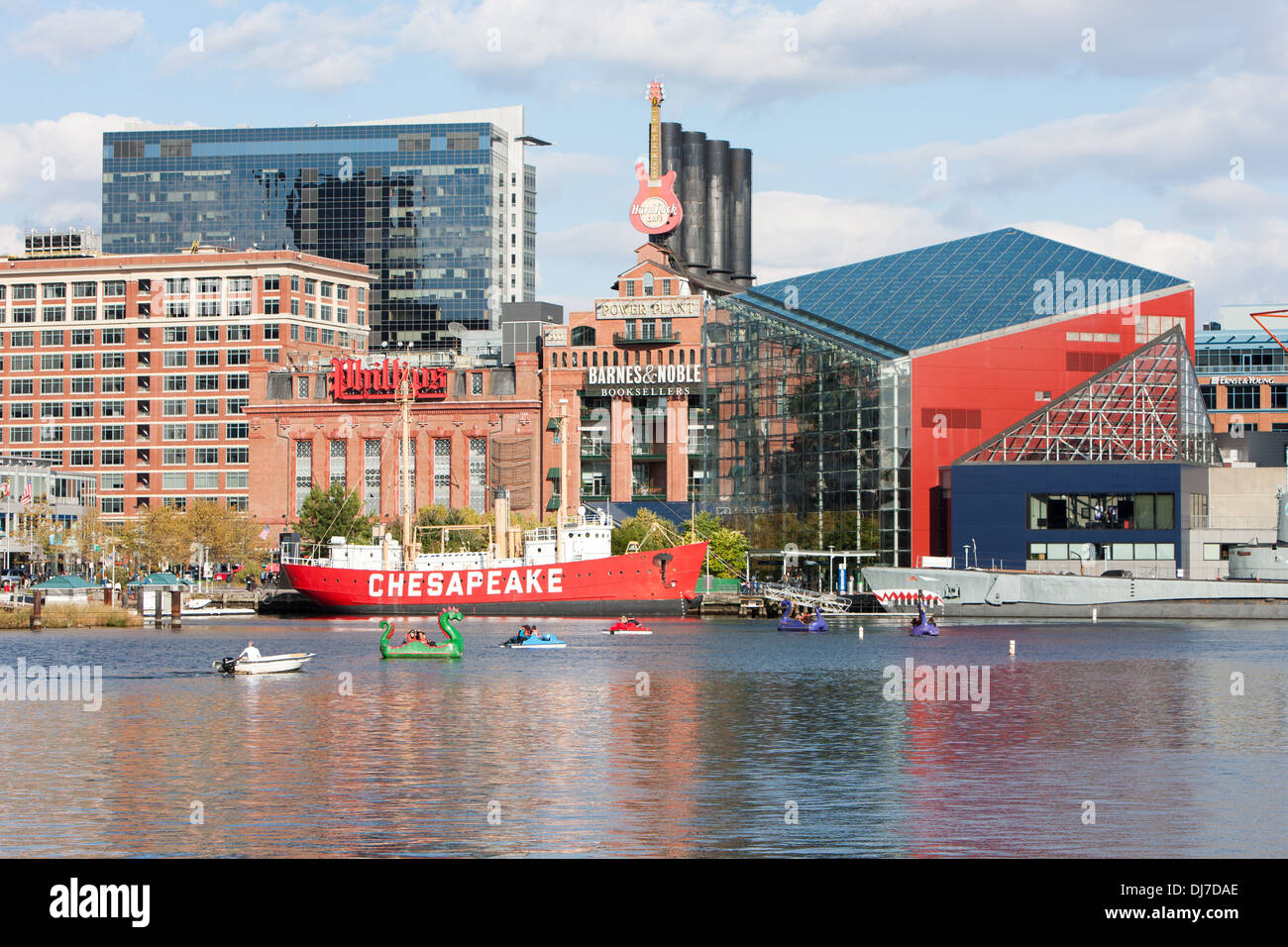 Tourists enjoy paddle boats near the National Aquarium and Lightship Chesapeake in the Inner Harbor in Baltimore, Maryland. - Stock Image