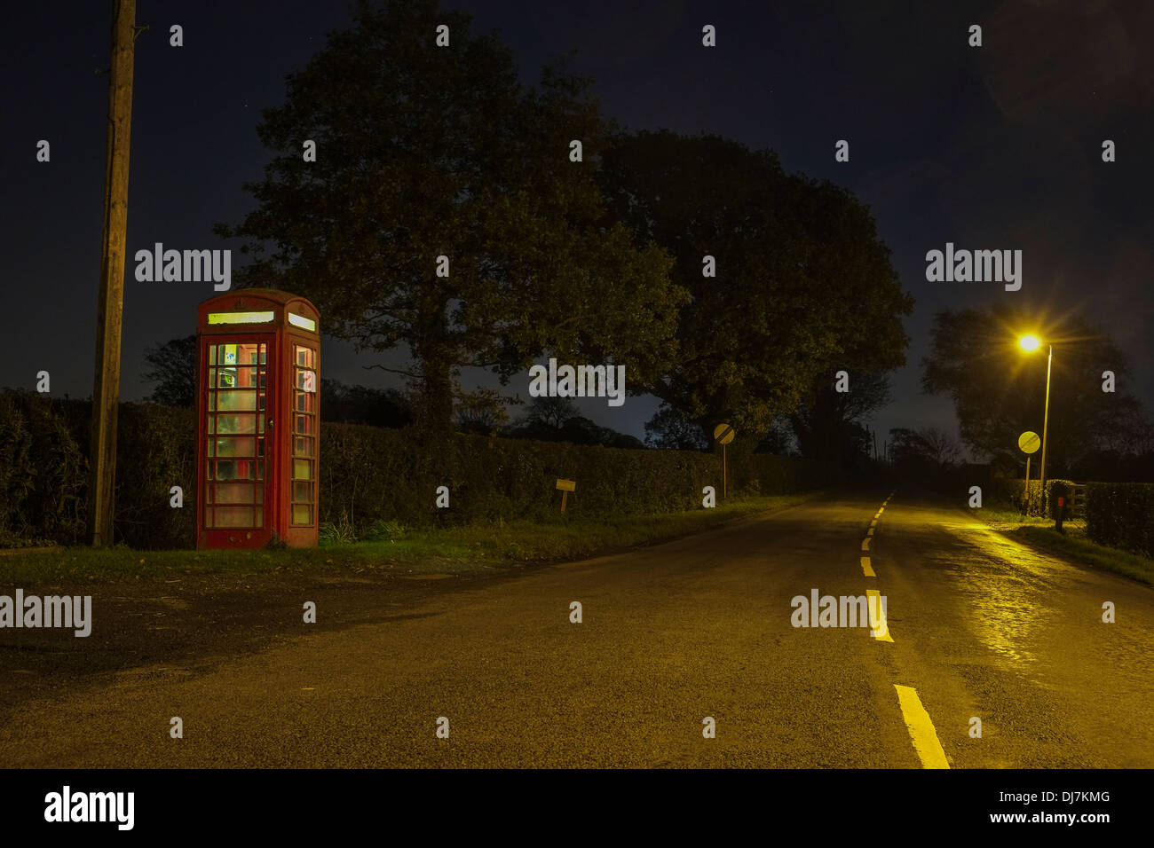 Lone Red Telephone box on a country lane at night - Stock Image