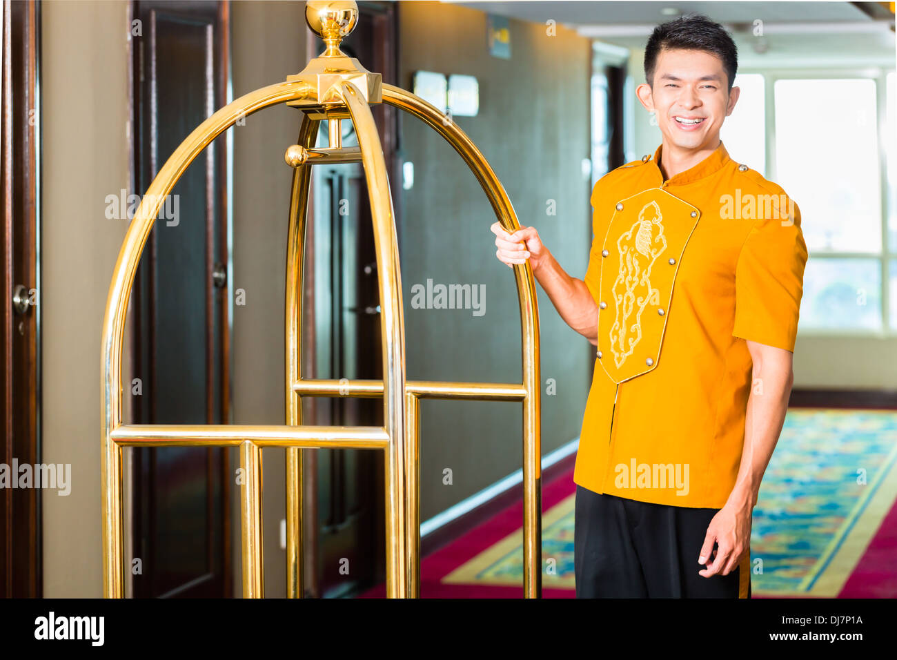 Asian Chinese baggage porter or bell boy or page bringing the suitcase of guests with a box van to the hotel room - Stock Image