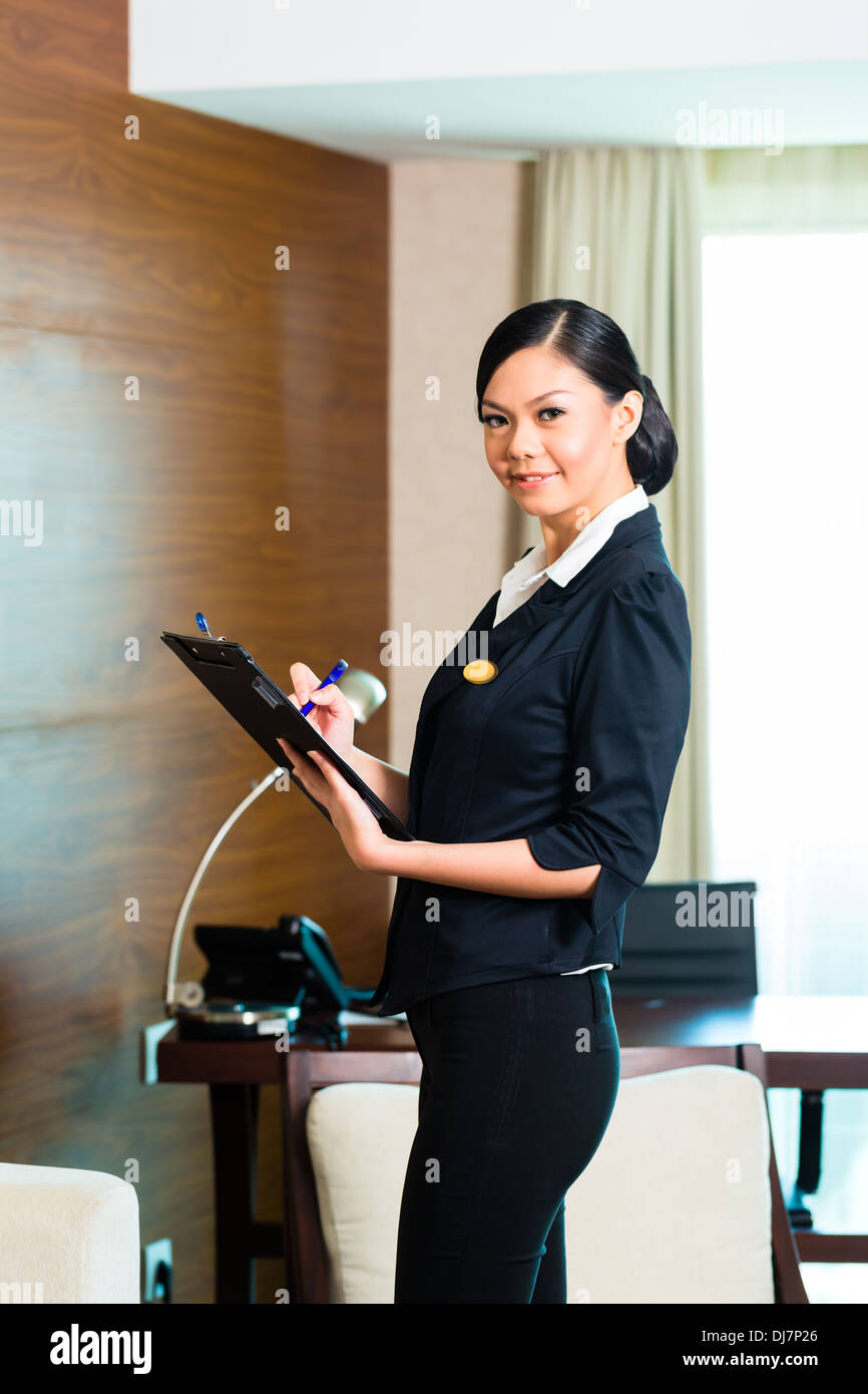 Housekeeping manager or assistant controlling or checking the room ...