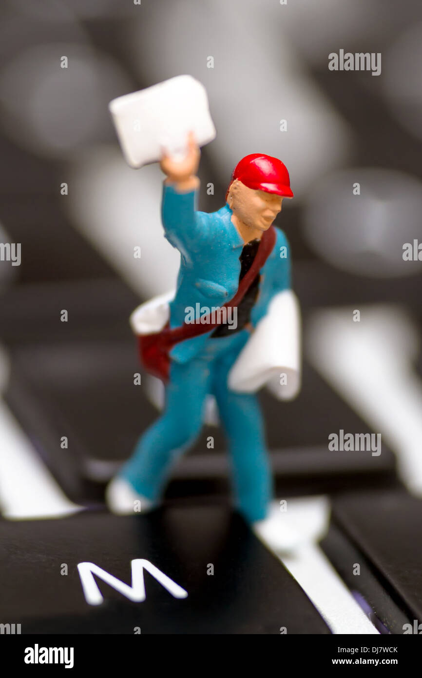 Miniature figure with newspaper on keyboard, symbolic picture for news, mail, epaper - Stock Image