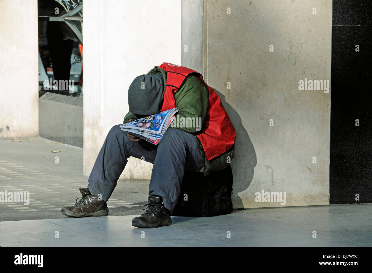 Big issue seller wrapped up warmly against the cold and asleep in the Winter sunshine, Central London, England UK - Stock Image