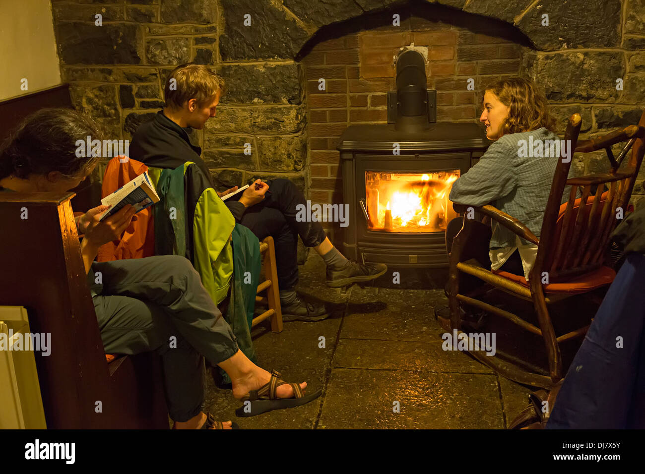 Relaxing in front of a peat fire in the hostel, Doolin, Co. Clare, Ireland - Stock Image