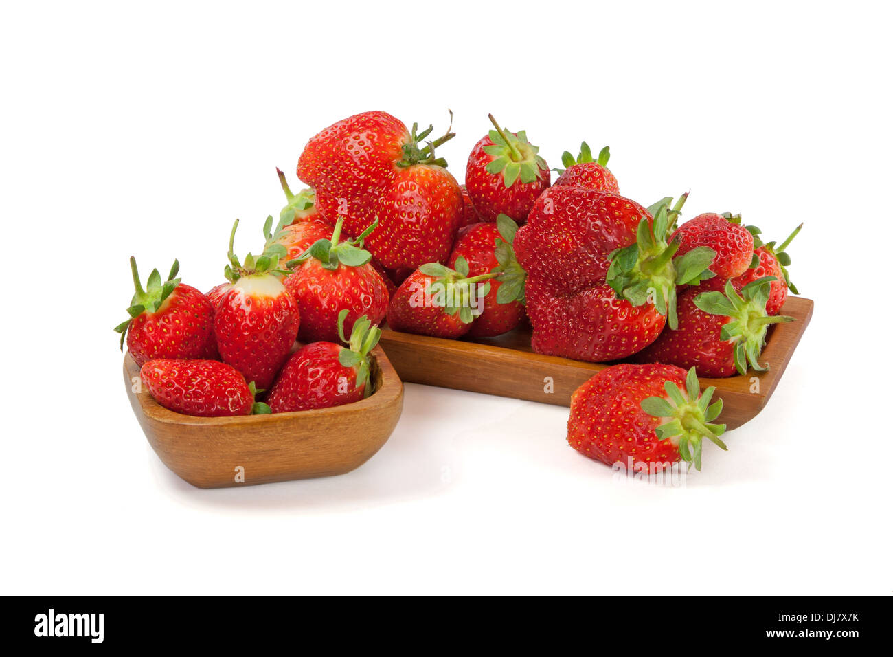 Strawberries in a wooden bowl isolated on white background - Stock Image