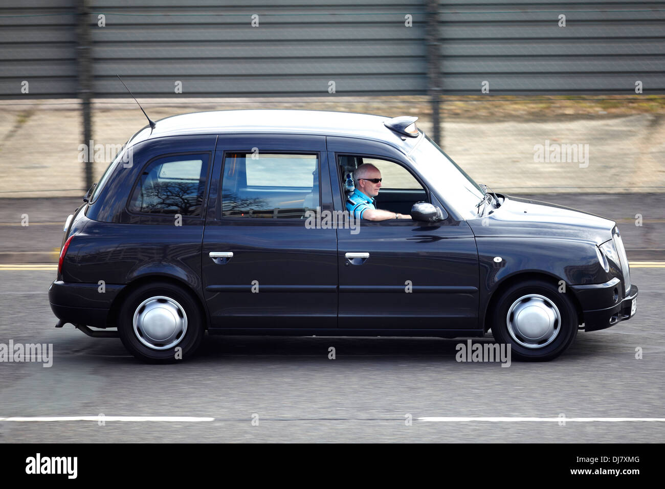 A hackney or hackney carriage (also called a cab, black cab, hack or London taxi) driving in London - Stock Image