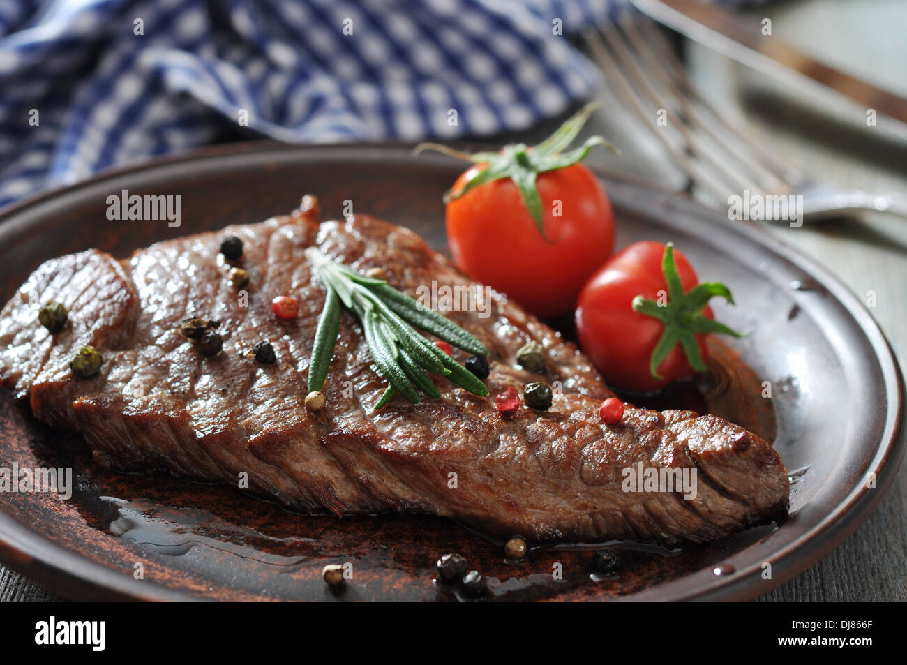 Grilled steak on plate with tomatoes, spices and rosemary closeup Stock Photo