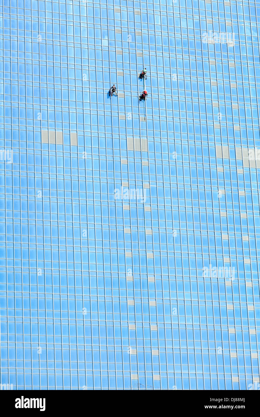 Industrial washers working on skyscraper mirror facade - Stock Image