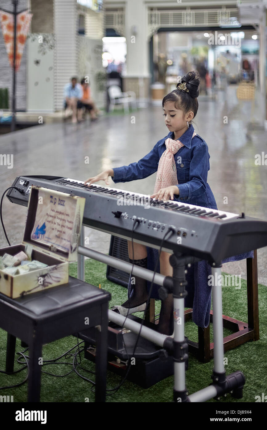 7 year old Thai protégé Suthasinee Hong Wongjindasak playing the electric piano at a shopping mall. Thailand S. E. Asia - Stock Image
