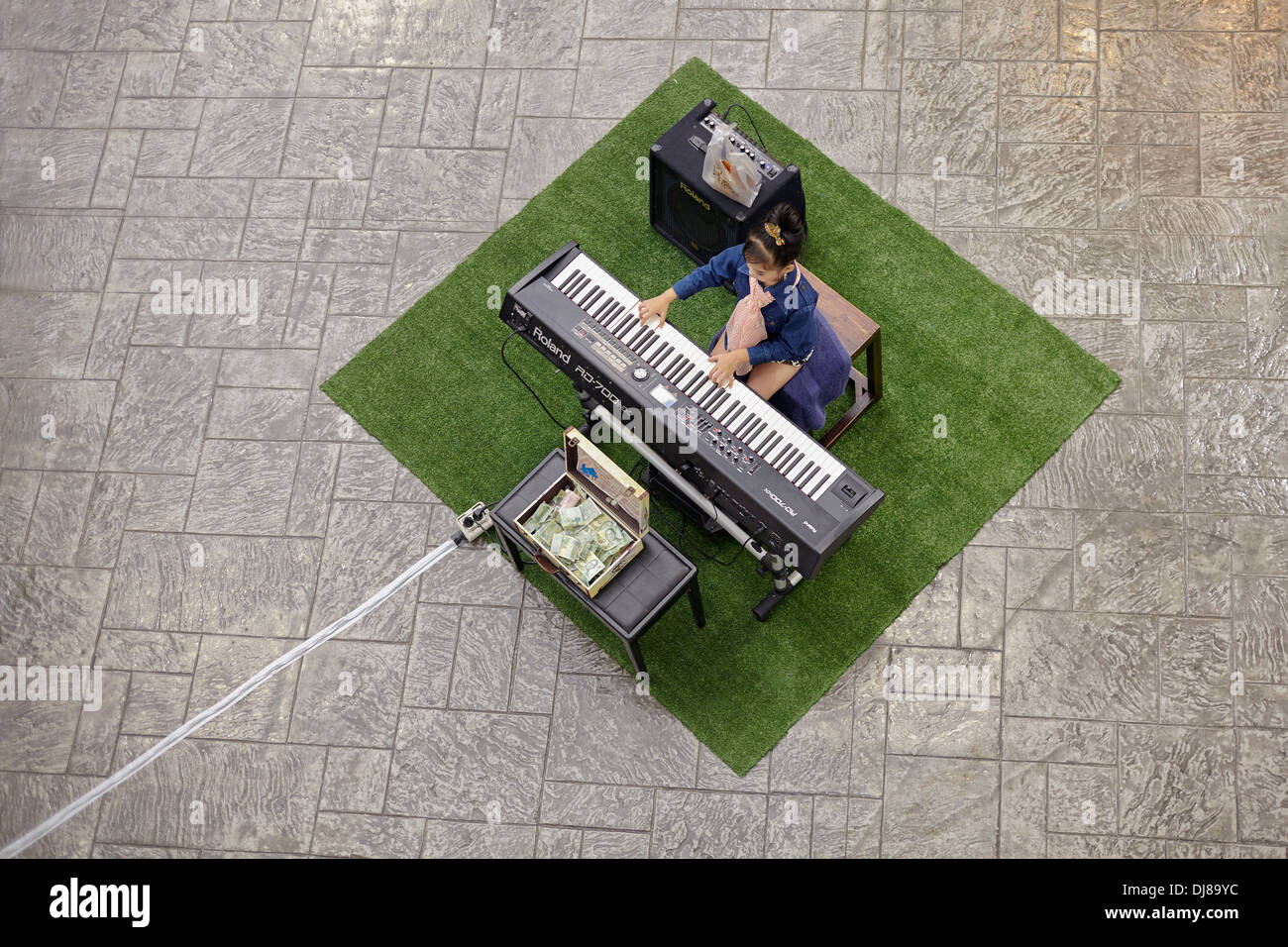 Overhead view of a young girl playing the electric piano in a shopping mall. - Stock Image