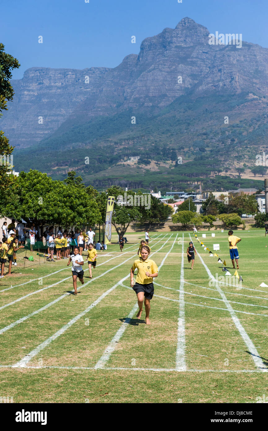 Girl running towards the finish line at a fields sports day, St Georges School, Cape Town, South Africa - Stock Image