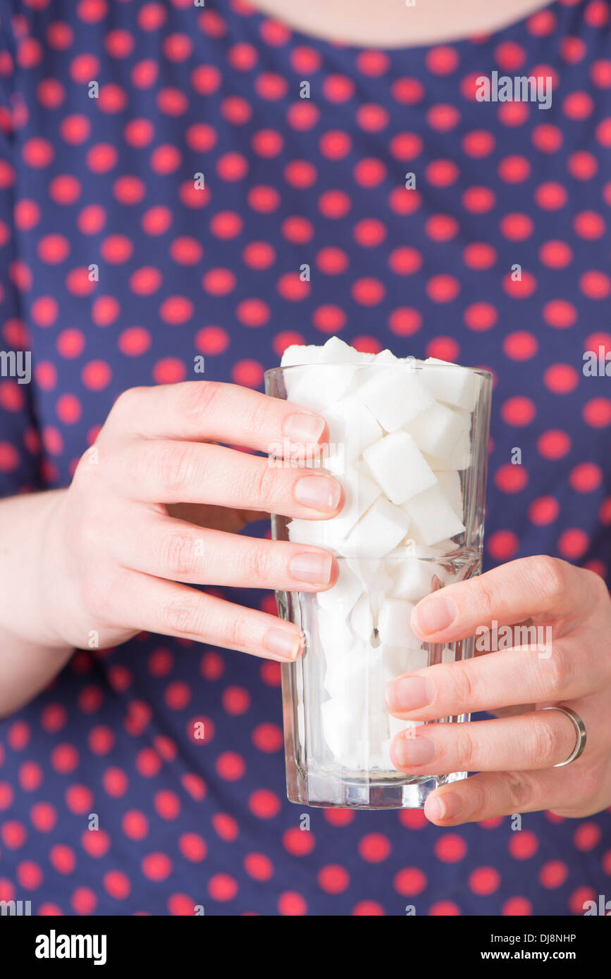 Woman holding a glass filled with sugar cubes - Stock Image