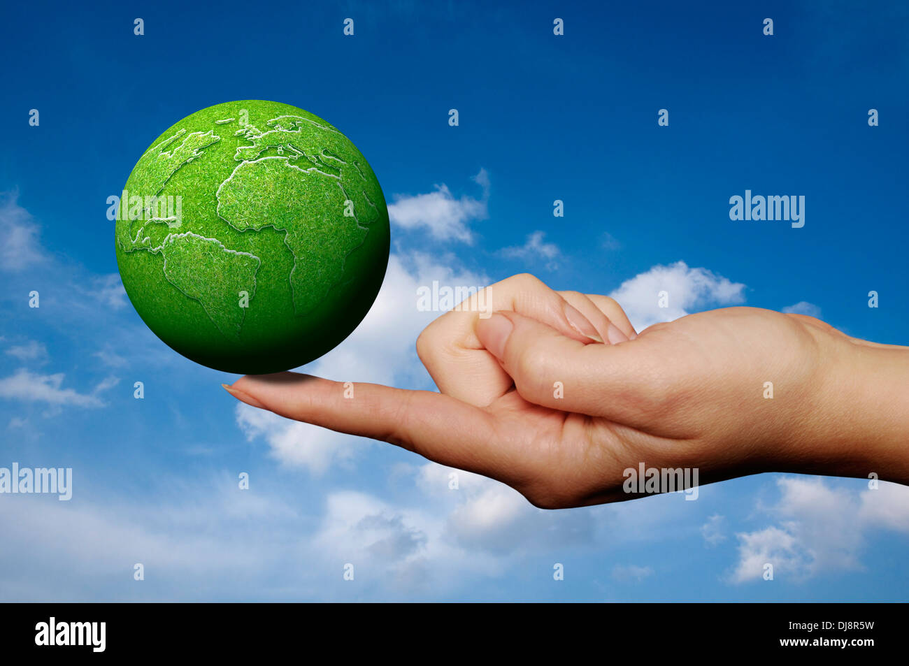 woman holding a green Earth on the tip of her finger - Stock Image