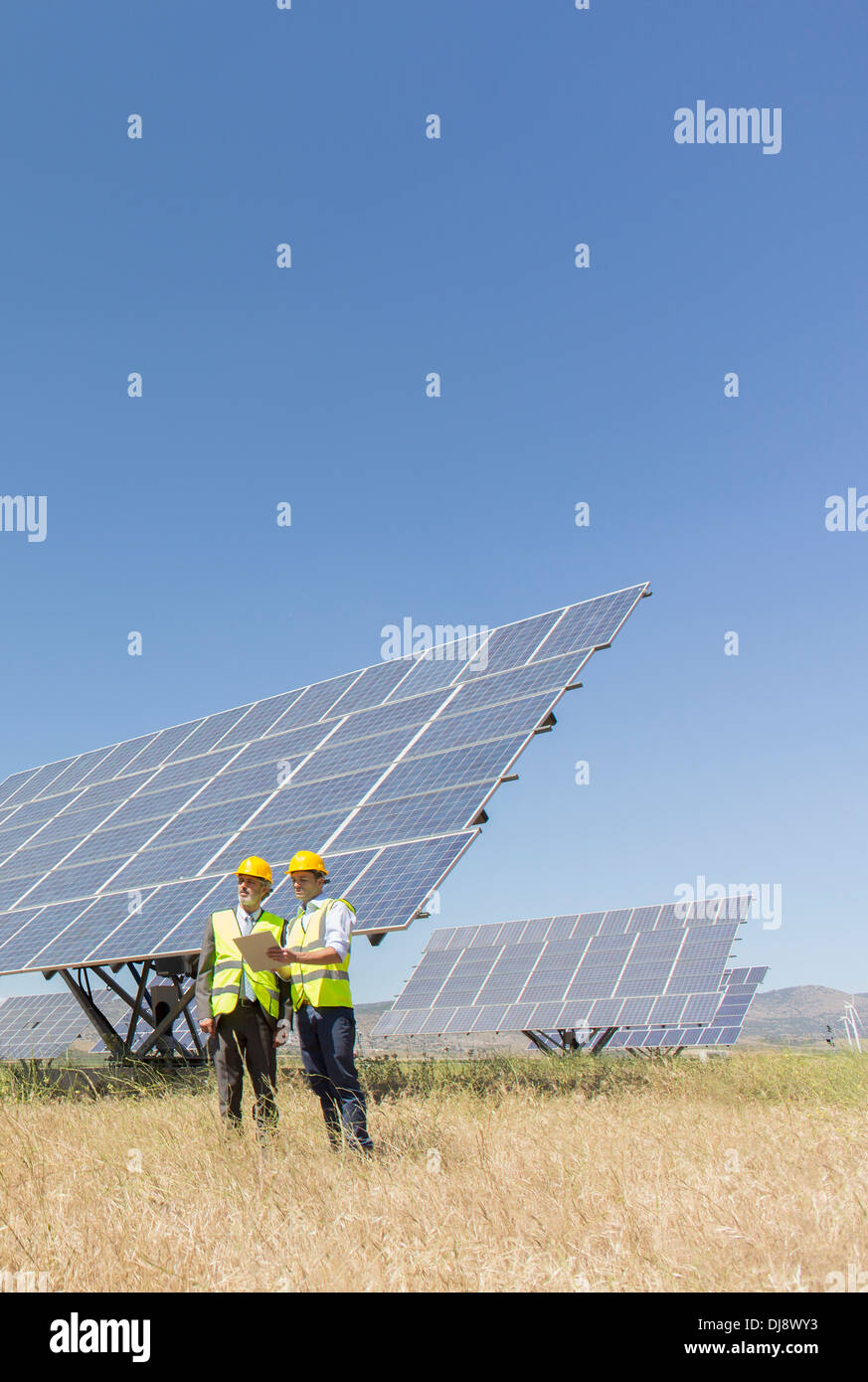 Workers standing by solar panels in rural landscape - Stock Image