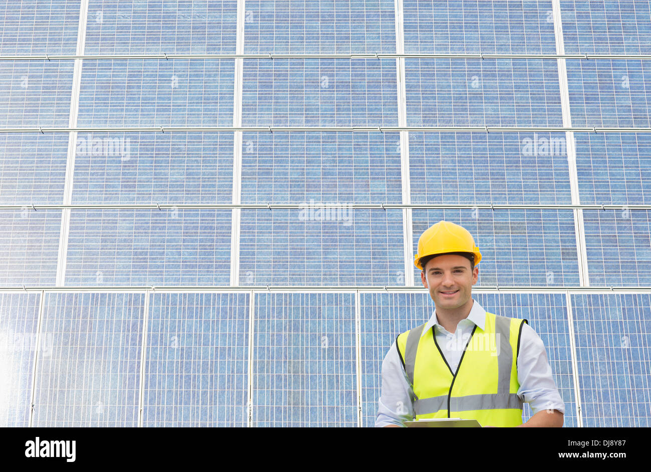 Worker standing under shade by wind turbine - Stock Image
