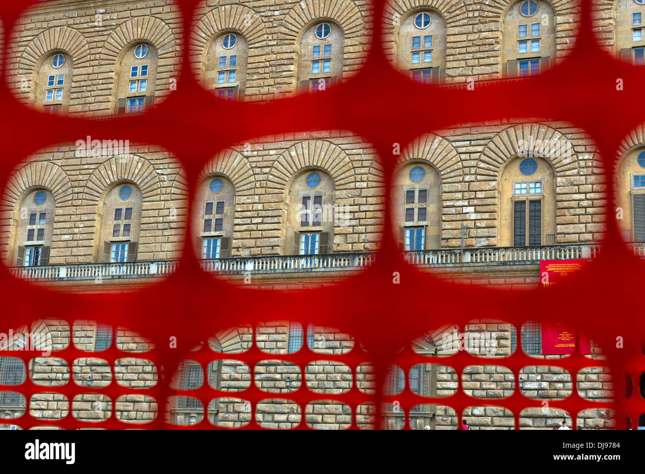 Window details of Pitti Palace seen through a red safety barricade, Florence, Italy - Stock Image