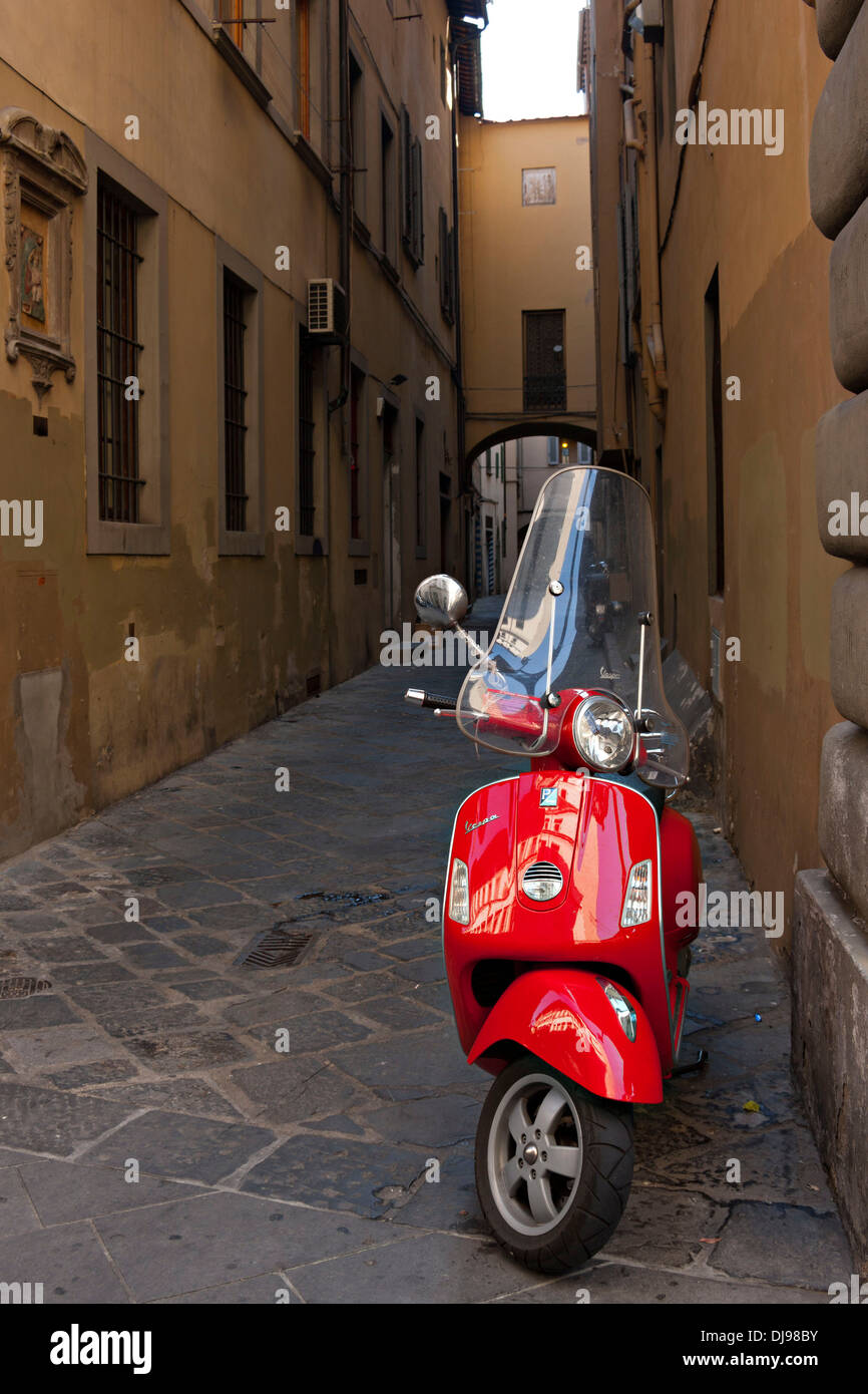 Red Vespa motor bike in lane, Florence, Italy - Stock Image