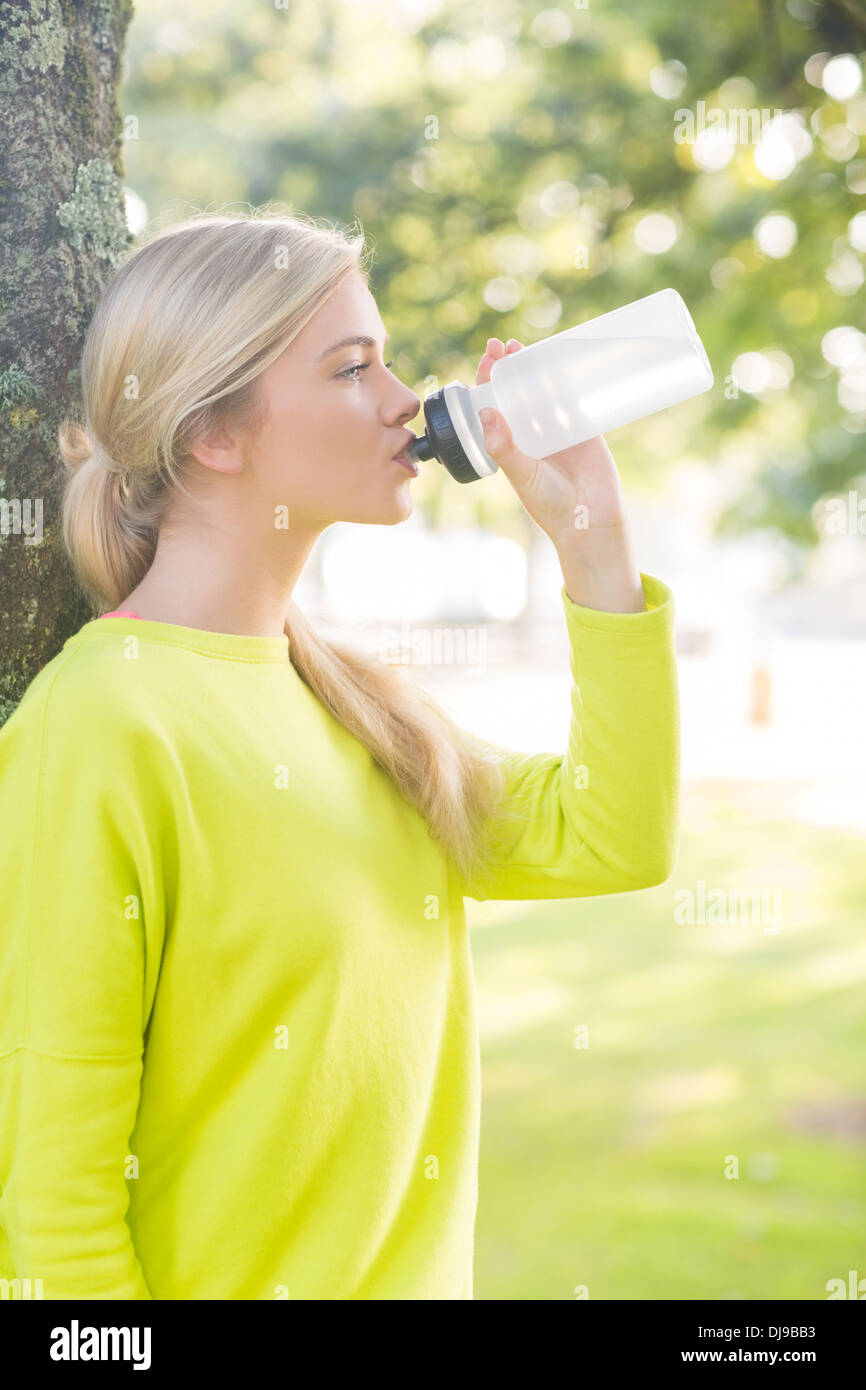 Fit calm blonde drinking from water bottle - Stock Image