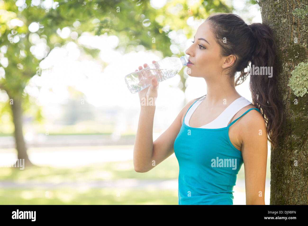 Active peaceful brunette drinking from a water bottle - Stock Image