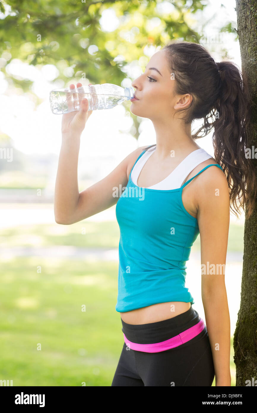 Active attractive brunette drinking from a water bottle - Stock Image