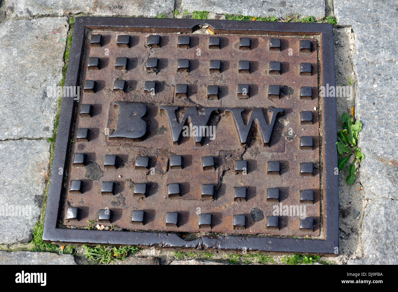 Manhole cover (BWW - Boston Water Works) in the streets of Boston, Massachusetts, USA - Stock Image