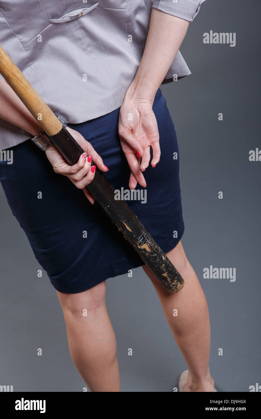 symbolic pictures of a decided and lying woman with baseball bat - Stock Image