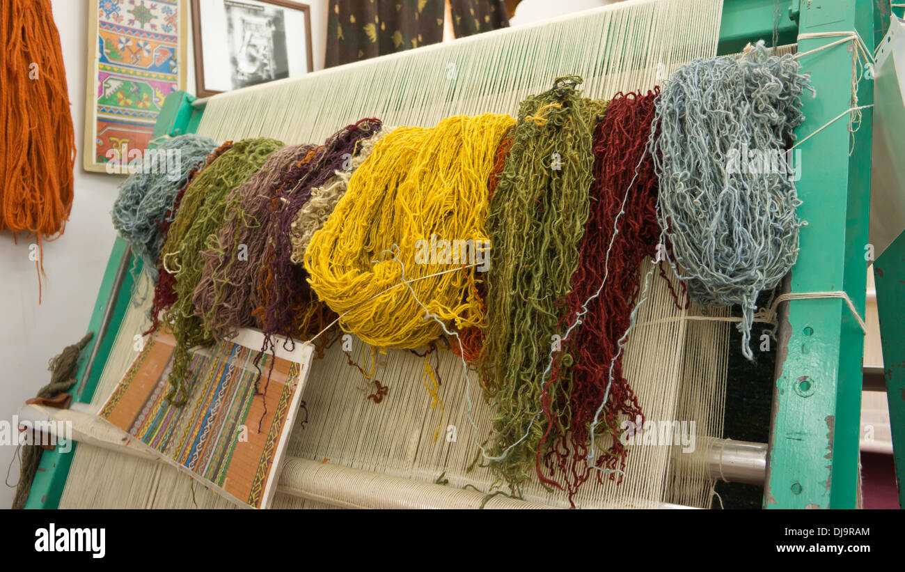 Coloured skeins of wool ready for carpet making on a loom. - Stock Image