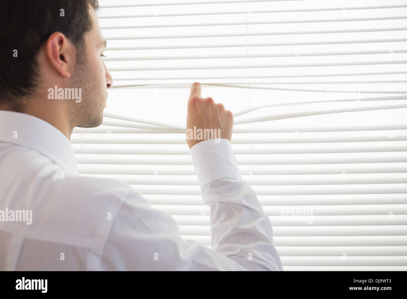 Rear view of handsome businessman spying through roller blind - Stock Image