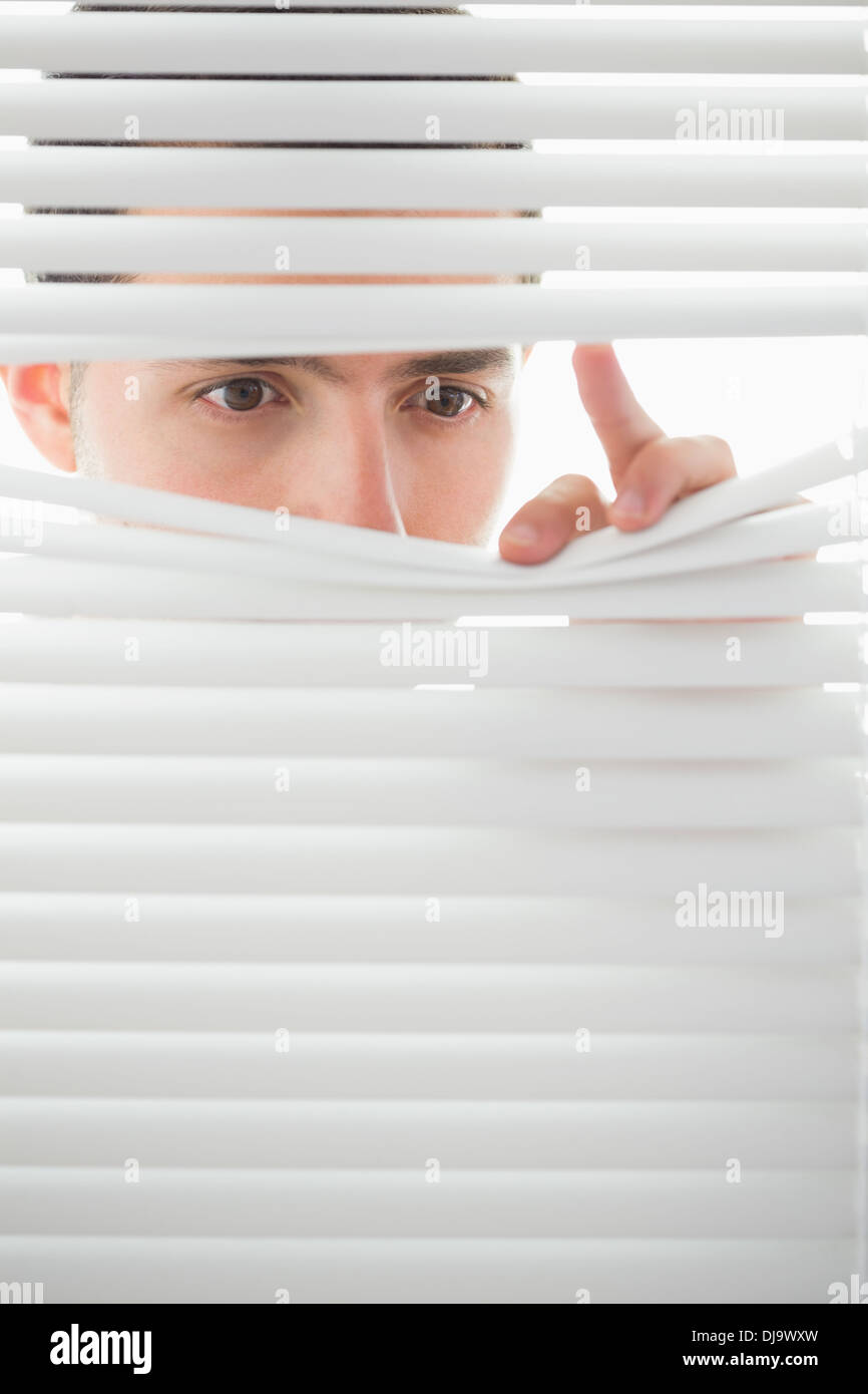 Serious male eyes spying through roller blind - Stock Image
