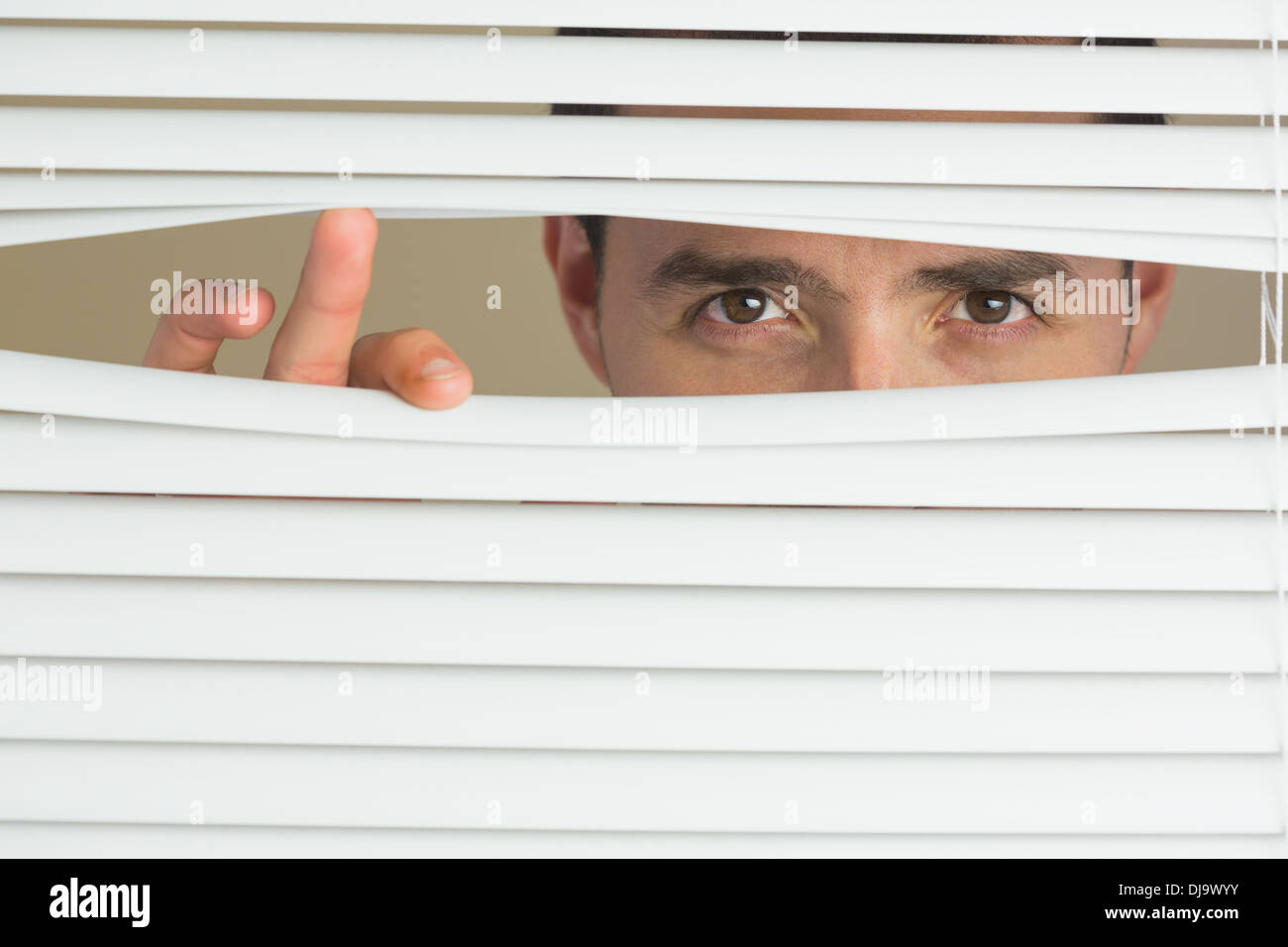 Focused male eyes spying through roller blind - Stock Image