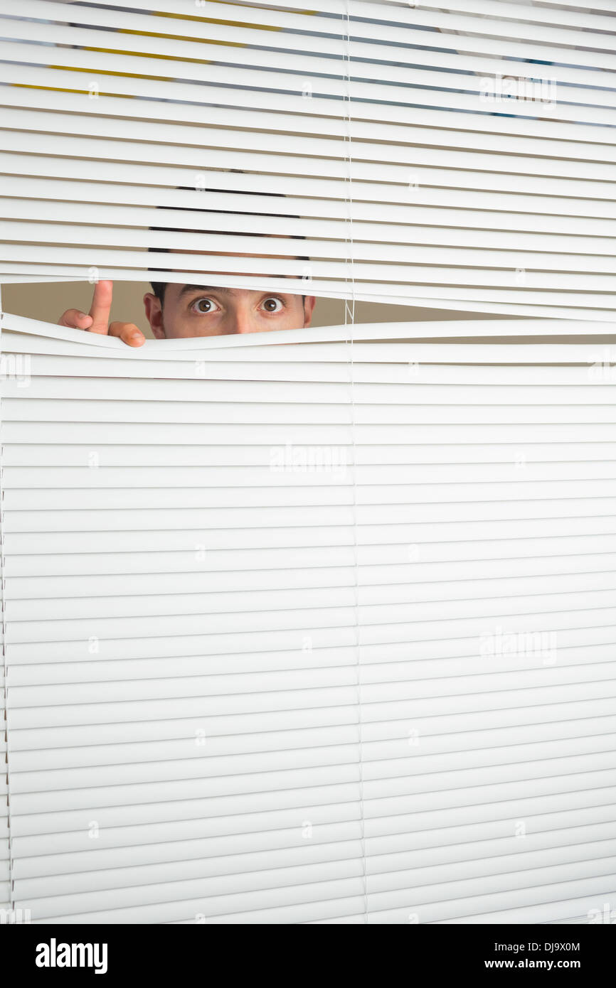 Astonished male eyes spying through roller blind - Stock Image