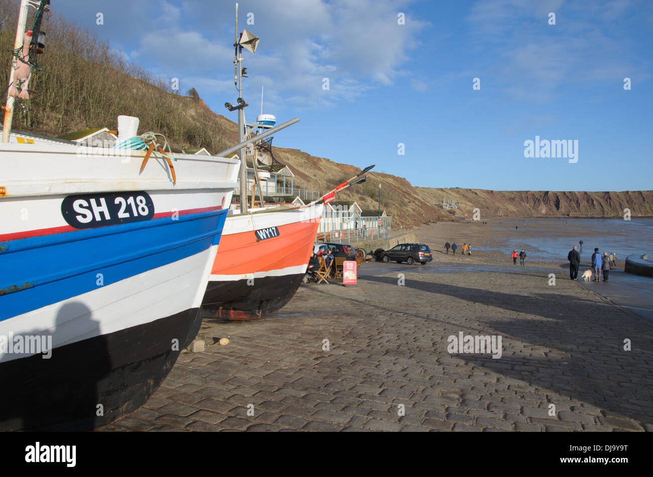 Inshore traditional fishing boats known as cobles on the slipway at the coastal seaside resort of Filey Stock Photo