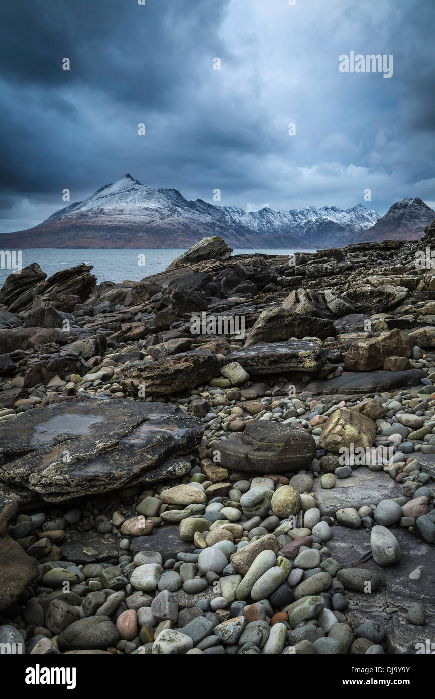 Elgol beach under a stormy sky with snow dusted Cuillin Hills in the background, Isle of Skye, Scotland - Stock Image