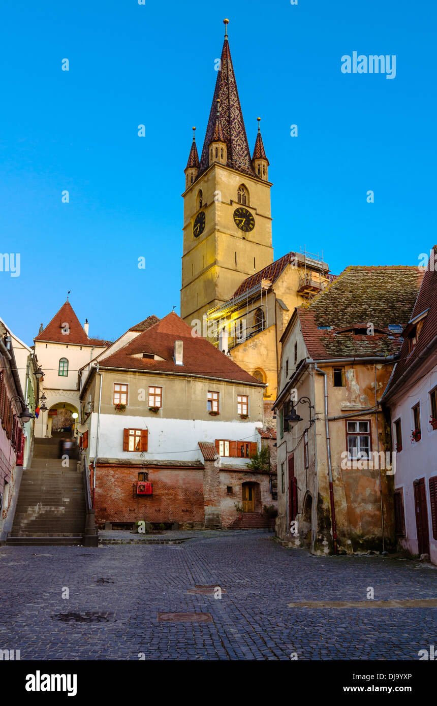 Medieval street with Evanghelical Church's famous tower, landmark of Sibiu - Stock Image