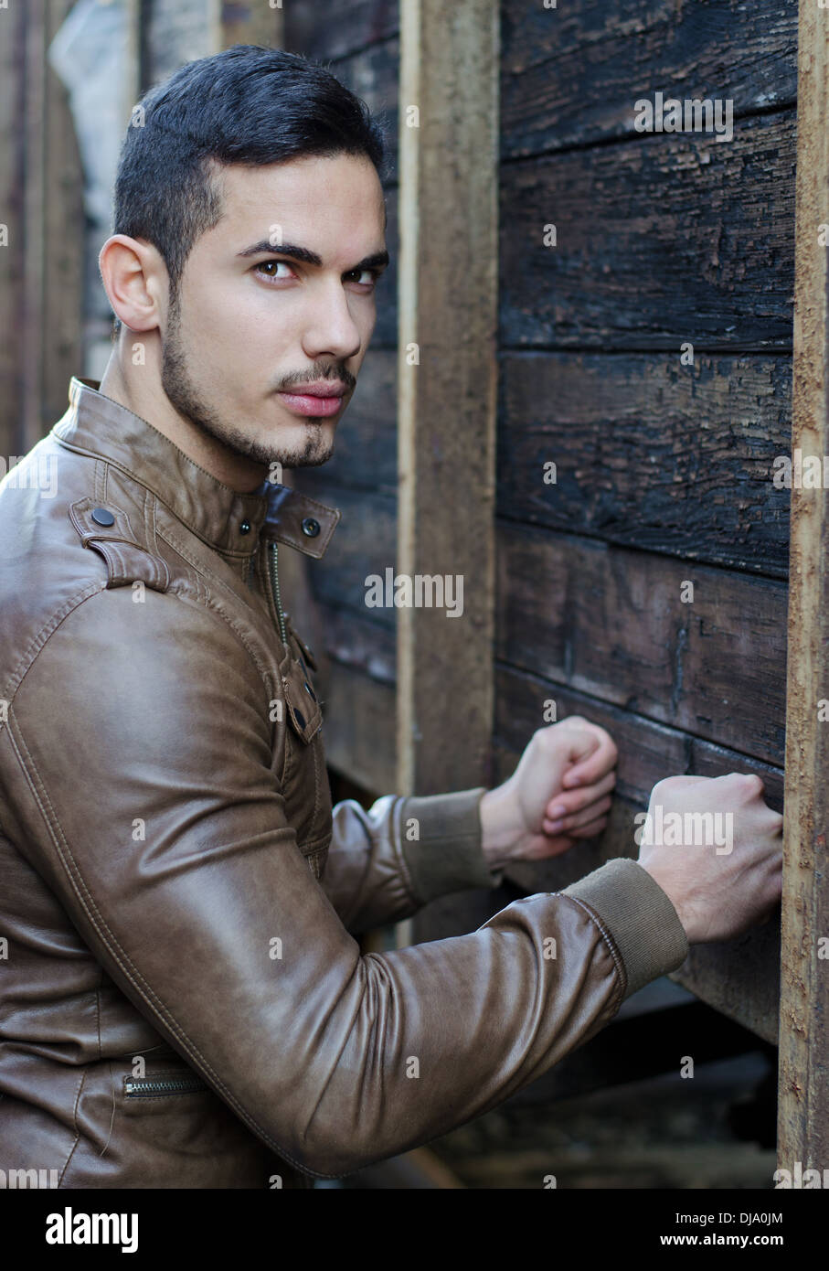 Handsome young man pressing fists on wood planks wall and looking at camera - Stock Image