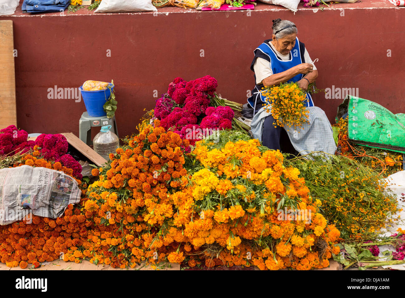 an elderly mexican woman selling flowers used for honoring