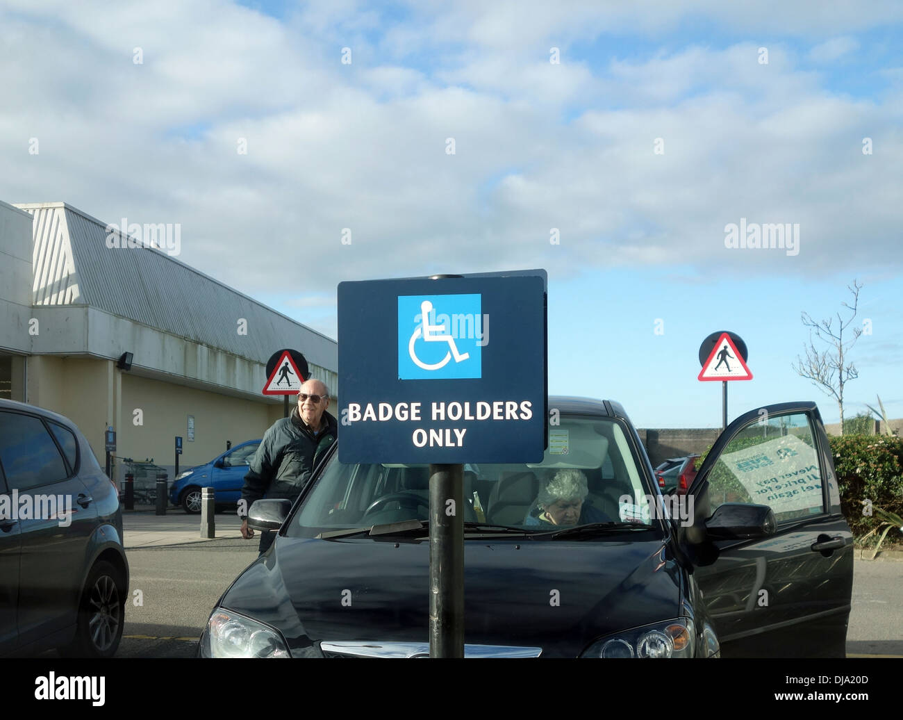 A car parked in a blue badge parking zone for disabled drivers - Stock Image