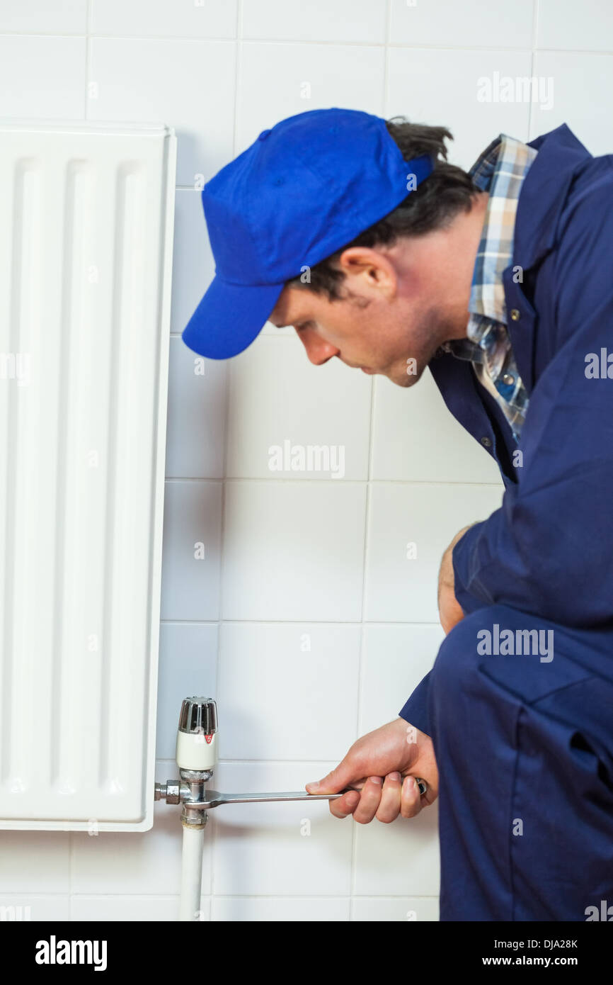 Serious handyman in blue coveralls repairing a radiator - Stock Image