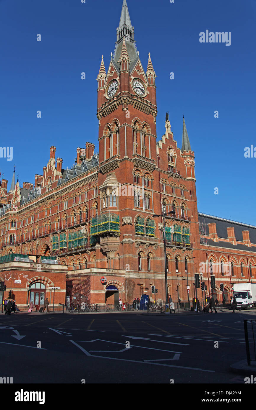 A side view of Saint Pancras railway station in London showing the large clock tower and old Hotel rooms along the front. - Stock Image